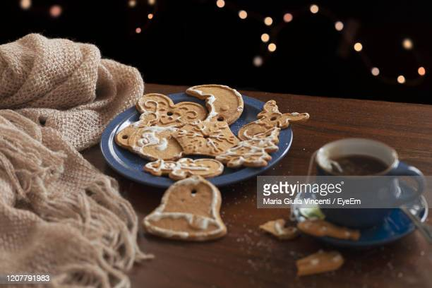 a table with spiced christmas cookies, a woolen scarf and a cup. lights bokeh in background. - maria giulia vincenti foto e immagini stock