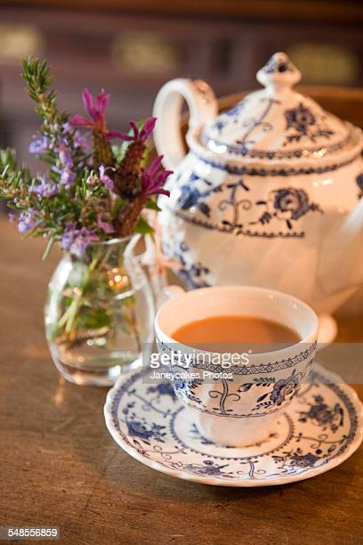 table with traditional teapot and teacup and saucer - britse cultuur stockfoto's en -beelden