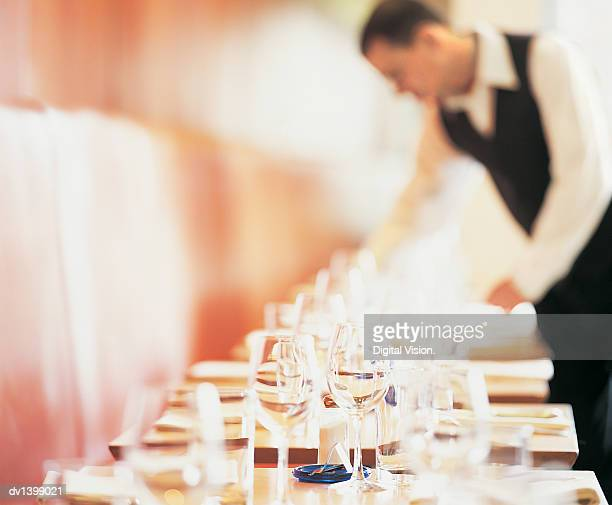 Table With Wineglasses in a Restaurant and a Waiter Clearing a Table in the Background