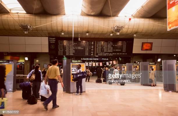 Tableau d'affichage des departs et guichet de billetterie automatique dans le hall de la gare de Montparnasse a Paris France