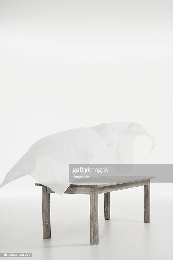 Tablecloth flying over table against white background : Stockfoto