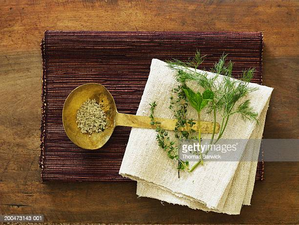 Tablecloth, place mat, fresh herbs and spoon filled with salt