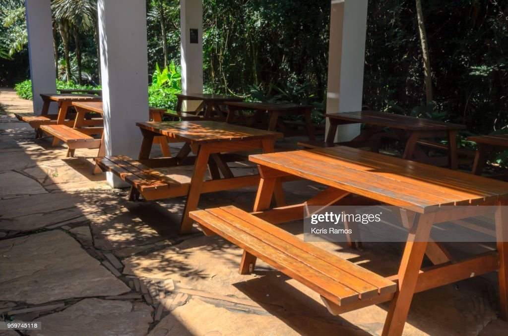 tables and benches made of light wood in patio for fast meals, free of people, on clear day of sun. : Stock-Foto
