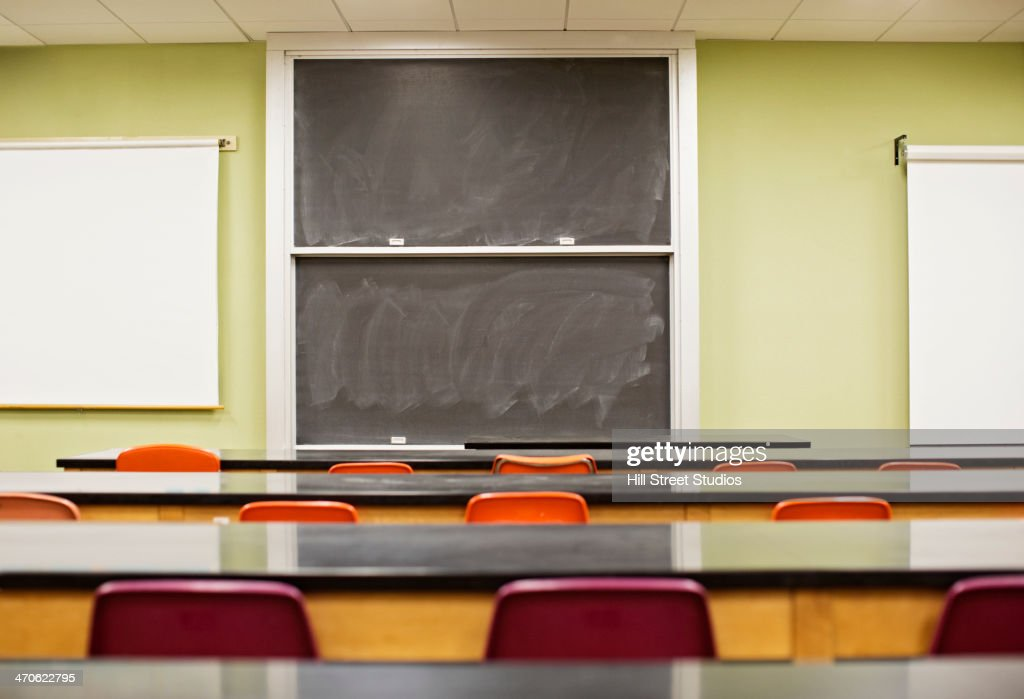 Tables and blackboard in empty lecture hall : Stock Photo