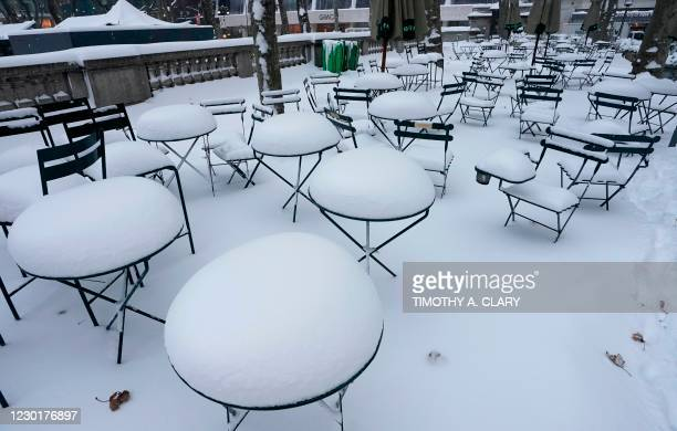 Tables and chairs are covered in snow at Bryant Park on December 17, 2020 in New York, the morning after a powerful winter storm hit the US...