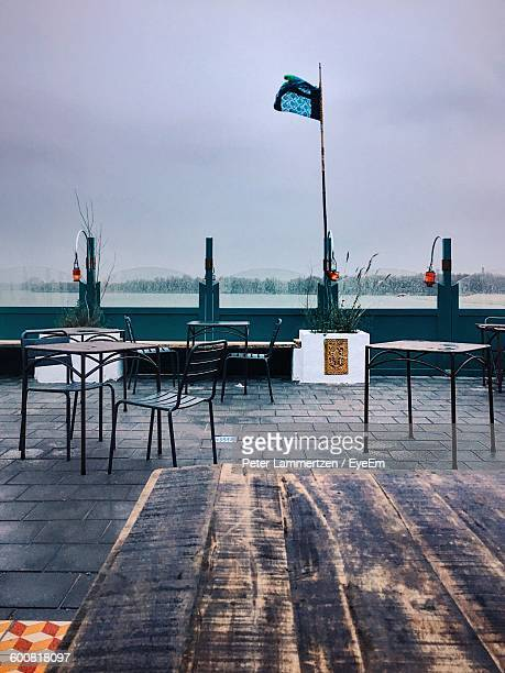Tables And Chairs Arranged At Sidewalk Cafe Against Sky
