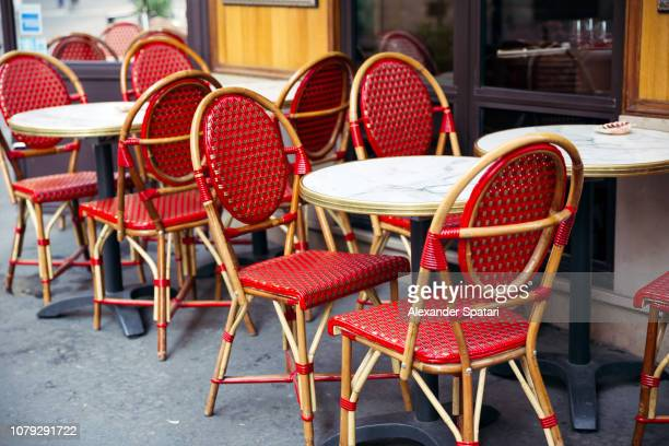 tables and chairs at traditional parisian sidewalk cafe, paris, france - franse cultuur stockfoto's en -beelden