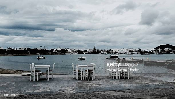 Tables And Chairs By Sea Against Cloudy Sky