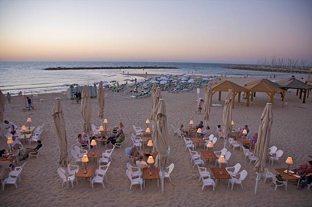 Tables and chairs on beach at dusk