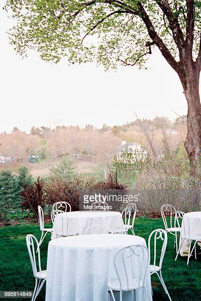 Tables and chairs set with white table clothes in a hotel garden overlooking a wooded valley.