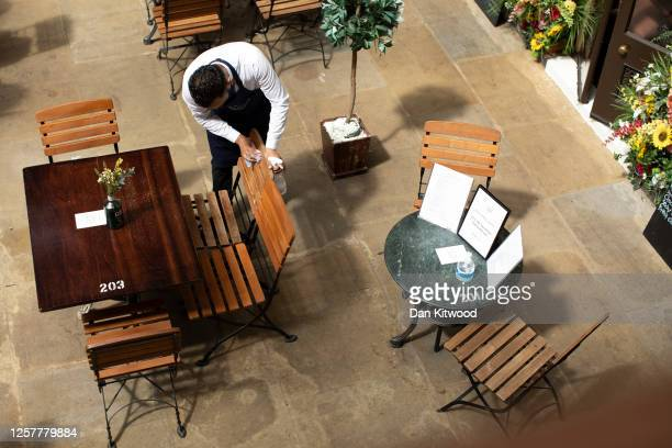 Tables are cleaned at a restaurant in Covent Garden on July 23, 2020 in London, England. The restaurant trade has been hit hard by the coronavirus...