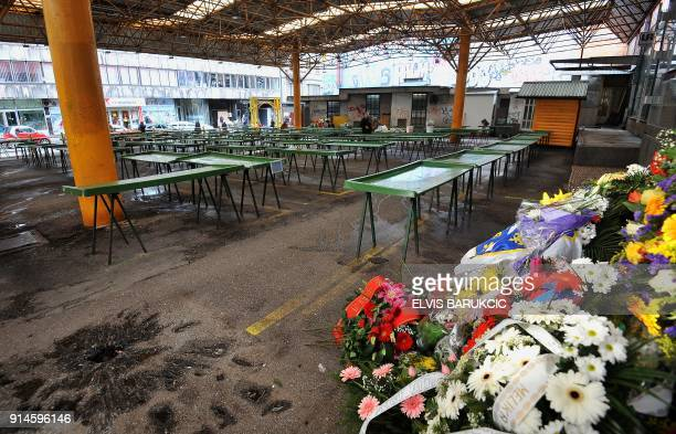 Tables are empty and floral tributes displayed at Sarajevo's main green market 'Markale' on February 5 2018 after it remained closed in commemoration...