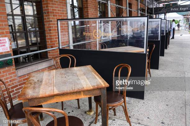 Tables separated by dividers are set outside Peter Luger Steakhouse in Williamsburg as the city continues Phase 4 of re-opening following...
