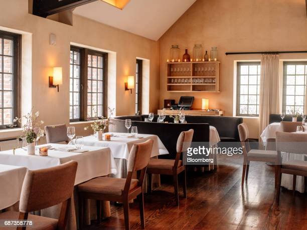 Tables sit inside the dining room of the Blue Hill at Stone Barns restaurant in Pocantico Hills New York US on Friday April 21 2017 As customers are...