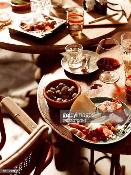 Tables with antipasto starters with olives, chorizo, salami, cheese, parma ham with beer and wine
