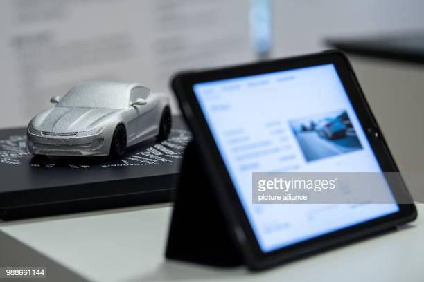 A tablet can be seen in front of a model of a car in Stuttgart Germany 29 November 2017 Photo Sebastian Gollnow/dpa