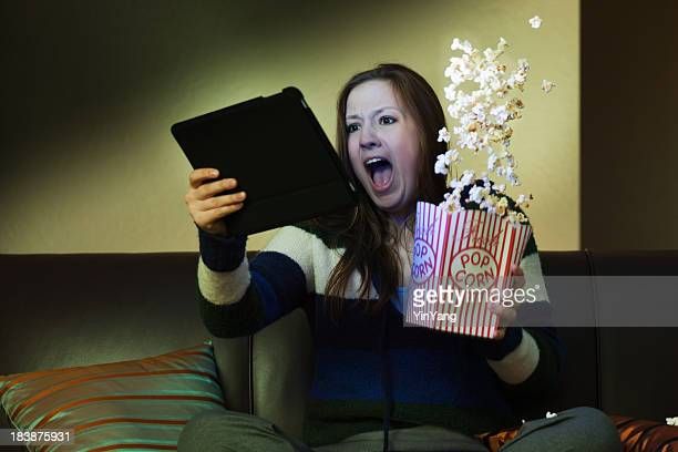 Tablet Computer Entertainment, Watching Scary Movie Screaming with Popcorn