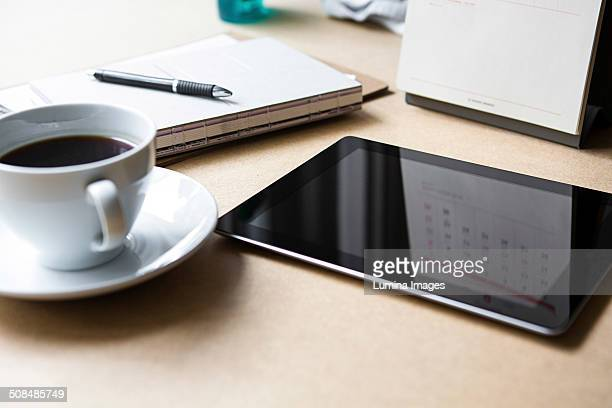 Tablet computer on table with book and coffee