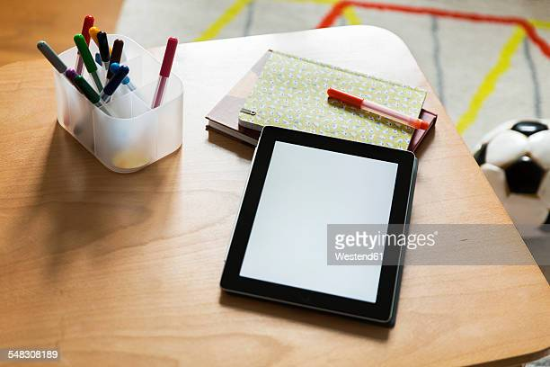 Tablet computer on wooden table in childrens room