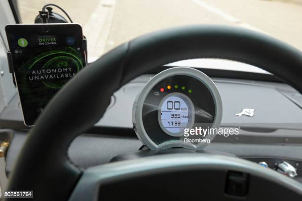A tablet device displays the current driving status of the CargoPod autonomous grocery delivery vehicle developed by Oxbotica Ltd during trials of...