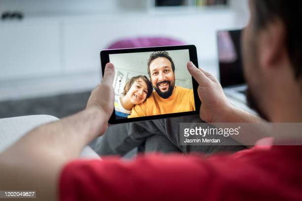 tablet is the best for video chat with family - mid adult men stock pictures, royalty-free photos & images