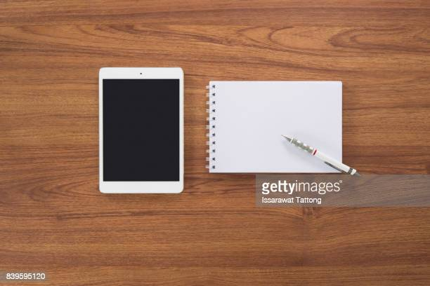 Tablet, notebook and pen on wooden desk, Top view