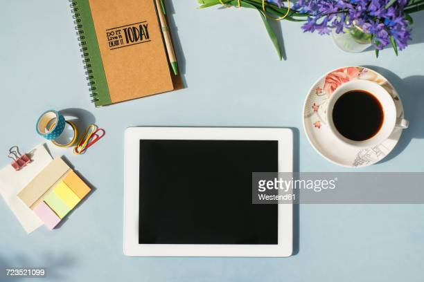 Tablet, notebook, office supplies, cup of coffee and spring flowers on light blue background