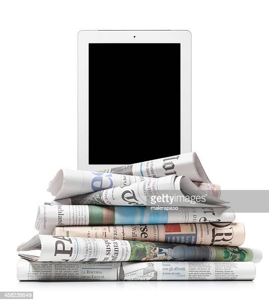 Tablet on stack of newspapers