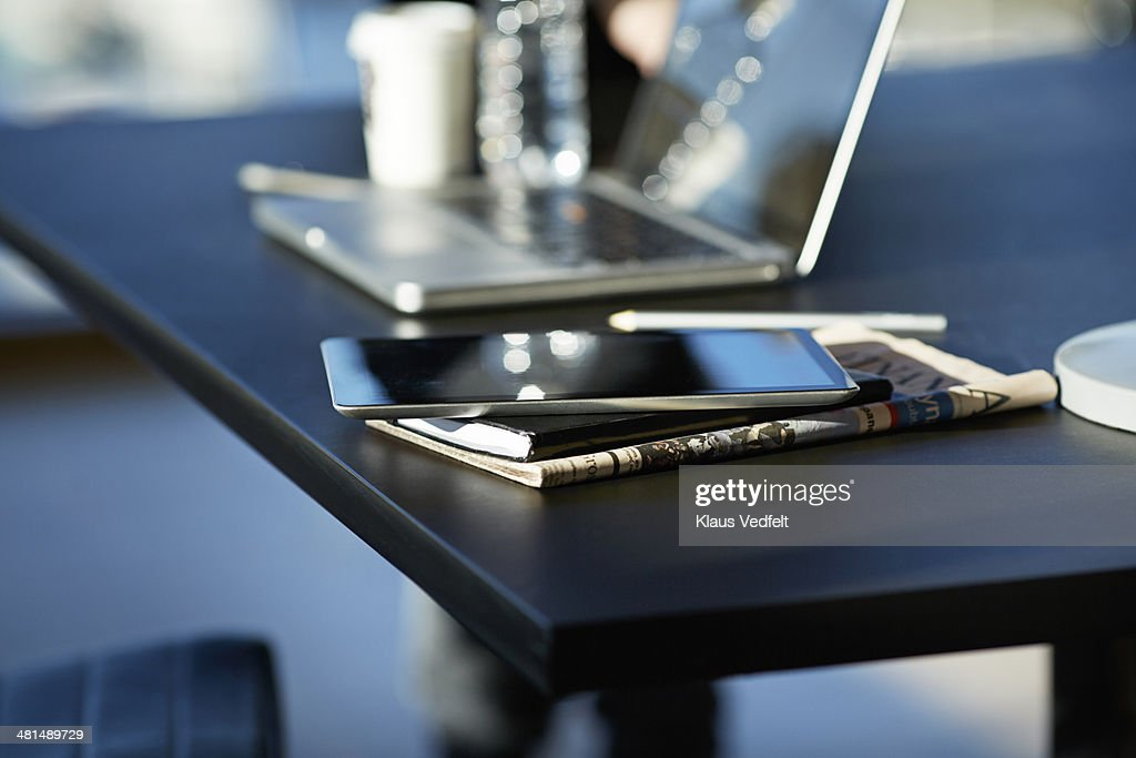Tablet on top of notebook and newspaper : Stock Photo