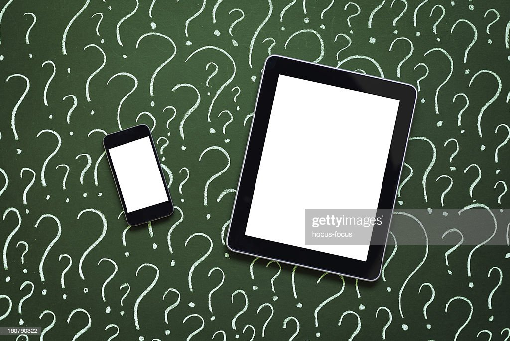 Tablet pc and smart phone in front of question marks : Stock Photo