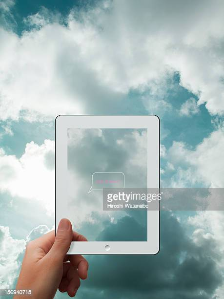 Tablet PC with cloudy sky in background