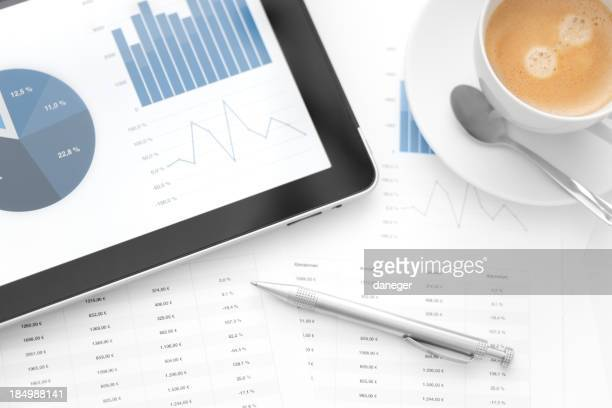Tablet showing charts next to worksheets a pen and coffee