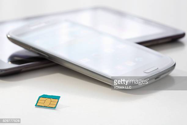 Tablet, smartphone and sim card on white