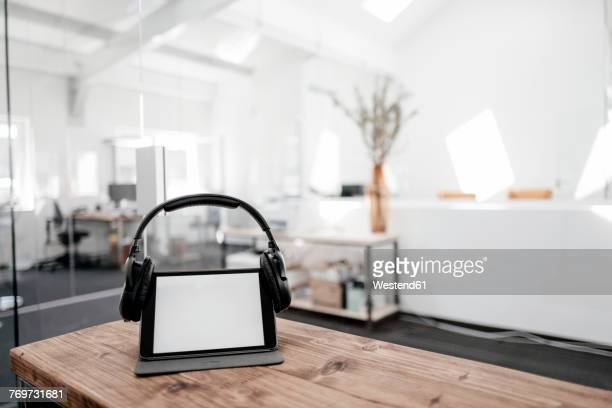Tablet with headphones on wooden table in office