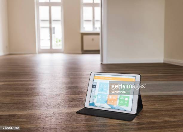 Tablet with smart home apps on wooden floor