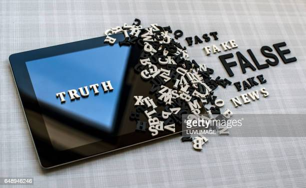 tablet with the wooden words truth, false and fake. - news event stock pictures, royalty-free photos & images
