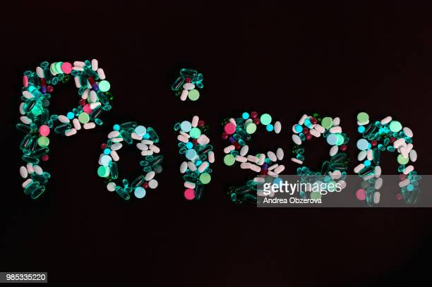 tablets, pills and capsules, that create word poison, on black background - bringing home the bacon stock photos and pictures