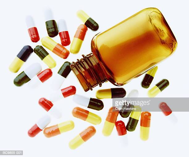 Tablets surrounding bottle against white background, close-up