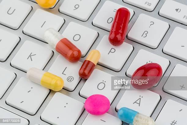 Tabletten auf Tastatur Symbolfoto für Online Apotheken und Arzneimittelkosten