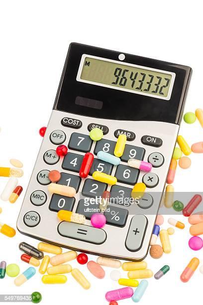 Tabletten liegen auf einem Taschenrechner Symbolfoto für Kosten in der Medizin und Pharmaindustrie