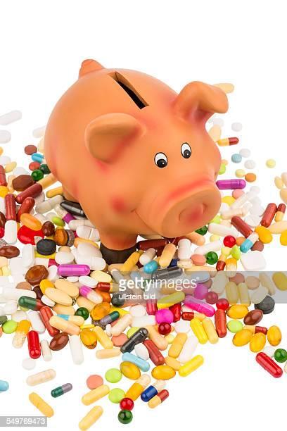 Tabletten liegen neben einem Sparschwein Symbolfoto für Kosten in der Medizin und Pharmaindustrie