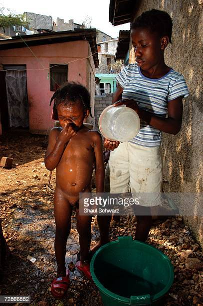 Tablita a 14yearold 'restavek' bathes fouryearold Marley Hill outside her 'host' family's home on March 30 2005 in PortauPrince Haiti Tablita worries...