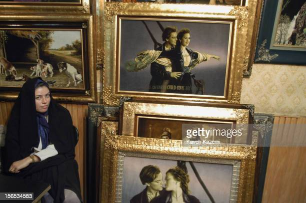 A woman in black chador sits next to paintings depicting Leonardo DiCaprio and Kate Winslet from the movie 'Titanic'