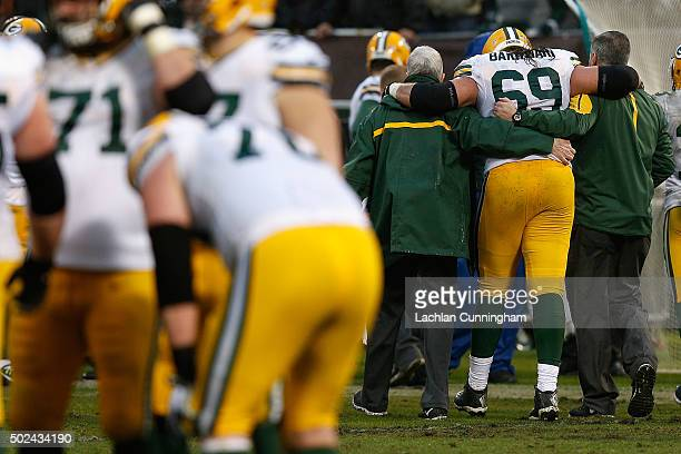 Tackle David Bakhtiari of the Green Bay Packers is assisted from the field in the fourth quarter against the Oakland Raiders at Oco Coliseum on...