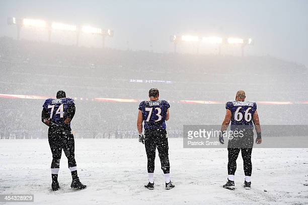 Tackle Michael Oher guard Marshal Yanda and center Gino Gradkowski of the Baltimore Ravens stand on the snow covered field during the national anthem...