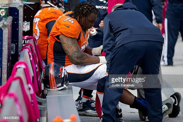Tackle Orlando Franklin of the Denver Broncos gets his leg looked at by the medical staff after going down during the third quarter against the...