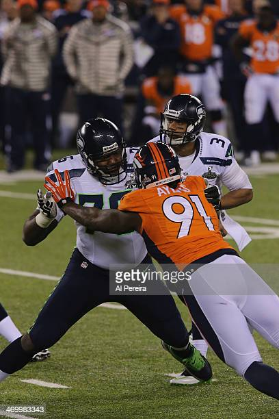 Tackle Russell Okung of the Seattle Seahawks blocks Defensive End Robert Ayers of the Denver Broncos in Super Bowl XLVIII at MetLife Stadium on...