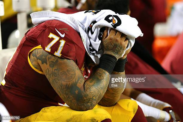 Tackle Trent Williams of the Washington Redskins covers his face with a towel against the Green Bay Packers in the fourth quarter during the NFC Wild...