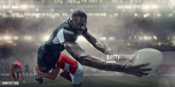 tackled rugby player in mid air about to score try - rugby stock pictures, royalty-free photos & images
