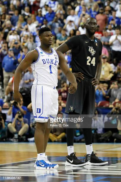Tacko Fall of the UCF Knights and Zion Williamson of the Duke Blue Devils look on during the first half in the second round game of the 2019 NCAA...